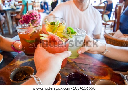 Friends toasting, saying cheers holding tropical blended fruit drinks #1034156650