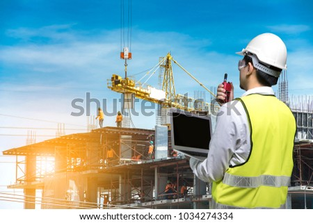 Engineer holding safety helmet in arms and holding walk talky in hands worker at construction site with sunrise background #1034274334