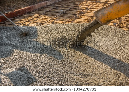 Pouring ready-mixed concrete after placing steel reinforcement to make the road by mixing mobile the concrete mixer. #1034278981