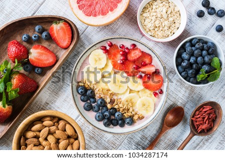 Smoothie bowl with banana slices, strawberry, blueberries, granola and pomegranate seeds. Top view. Healthy lifestyle, healthy eating, dieting, weight loss concept #1034287174