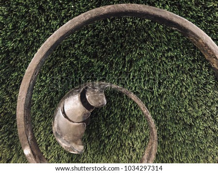 An artificial green grass with metal fence patterns #1034297314