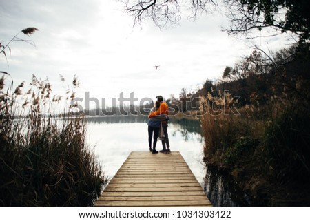 Young hipster couple of millennial teenagers, boyfriend and girlfriend stand on pier or boardwalk in park or forest, watch sunset over lake or river cuddle and hug in relationship goals manner #1034303422