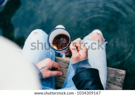 Over shoulder shot of trendy hipster man with hand tattoos sit on edge of water, sea or ocean, in blue denim jeans, hold metal camping mug or cup with black american coffee #1034309167
