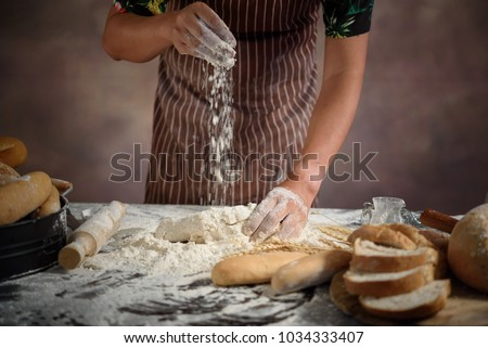 baker prepares bread. baker sprinkle and eggs the dough with flo #1034333407