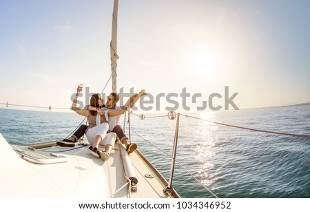 Young couple in love on sail boat with champagne at sunset - Happy people lifestyle on exclusive luxury concept  - Soft backlight focus on warm afternoon sunshine filter - Fisheye lens distortion #1034346952