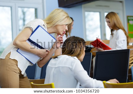 manager watching over the shoulder of trainee using computer #1034356720