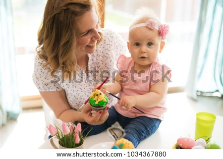 Mother and daughter kid painting easter eggs #1034367880