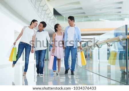 Cheerful Vietnamese family of four walking in mall with many shopping bags #1034376433