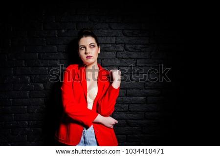 Stylish brunette girl on red jacket against studio black brick wall. #1034410471