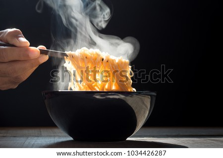 Hand uses chopsticks to pickup tasty noodles with steam and smoke in bowl on wooden background, selective focus. Asian meal on a table, junk food concept #1034426287