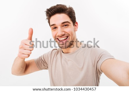 Photo of handsome man in casual t-shirt and bristle on face smiling on camera with thumb up while taking selfie isolated over white background #1034430457