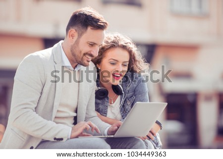 Young couple using a laptop outdoors and looking happy. #1034449363