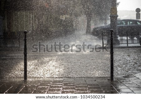 Rain in the city. Road, pavement, car in rain, close up. Water splashes, spills on roadway. #1034500234
