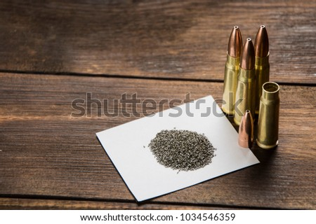 cartridge, bullet, cartridge case and gunpowder on a wooden table #1034546359