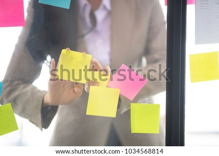 Creative businesswoman putting her ideas on glass during a presentation in meeting room. Setup studio shooting. #1034568814