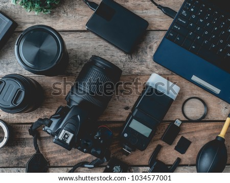 top view of work space photographer with digital camera, flash, cleaning kit, memory card, external harddisk, USB card reader and camera accessory on wooden table background. #1034577001