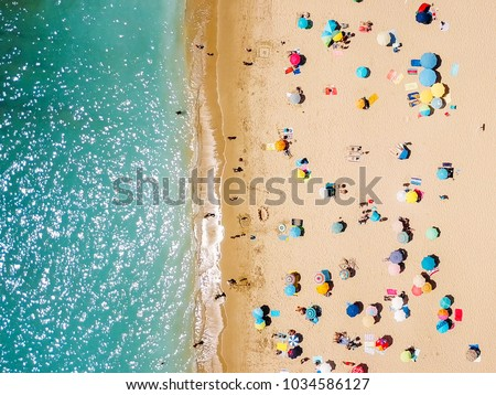 Aerial View From Flying Drone Of People Crowd Relaxing On Beach In Portugal #1034586127