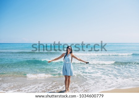 Smiling girl with long brown hair and in sunglass dancing on the beach with earphones and phone in hand. Aqua blue sea on background #1034600779