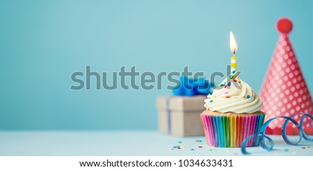 Birthday party background with cupcake, party hat and present Royalty-Free Stock Photo #1034633431