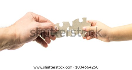 Hand of an adult and child with puzzles on a white background. Isolated. The concept of mutual understanding with the child. #1034664250