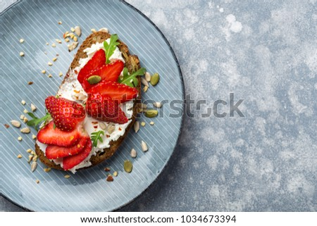 Top view of a plate with healthy rye bread sandwich with cream cheese and strawberry #1034673394