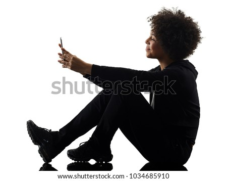 one mixed race african young teenager girl woman using telephone in studio shadow silhouette isolated on white background Royalty-Free Stock Photo #1034685910