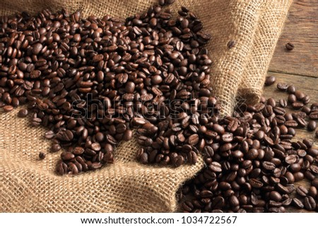 Fresh roasted coffee beans on a wooden table top.  #1034722567