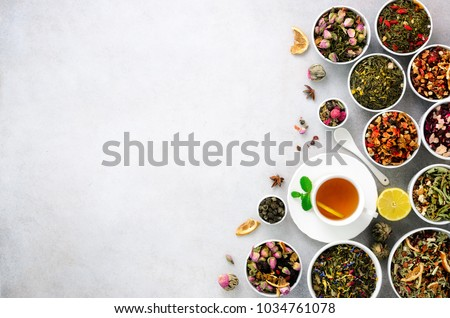 Assortment of dry tea in white bowls. Tea types backgound: green, black, floral, herbal, mint, melissa, ginger, apple, rose, lime tree, fruits, orange, hibiscus, raspberry, cornflower, cranberry. #1034761078
