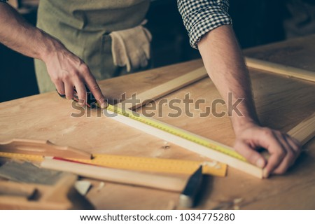Cropped close up photo of cabinet-maker's strong hands, the master is measuring a wooden frame using roulette on the work-table