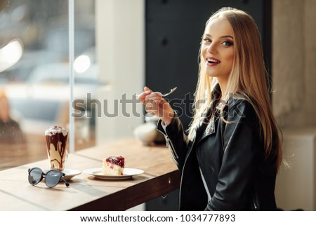 Pretty girl hold a plate of delicious cake and waer glasses. Sun shine photo with girl eat her cake #1034777893