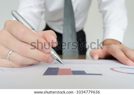 A man pointing with a pan to a chart and graphics on a piece of paper during a business meeting #1034779636