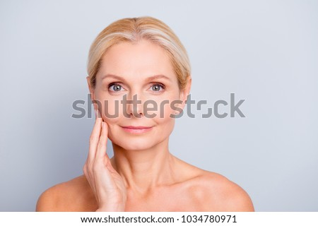 Portrait of pretty, attractive, charming, naked, nude woman touching her  perfect skin, isolated on grey background,  after peeling, lotion, mask, perfection, wellness, wellbeing, hydration concept #1034780971