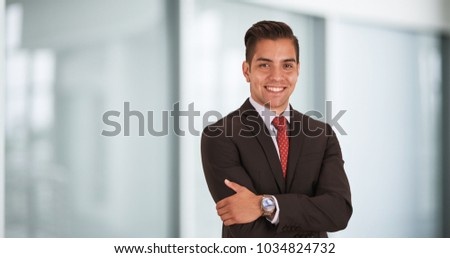 Happy smiling young Hispanic businessman standing in office with arms crossed looking at camera #1034824732