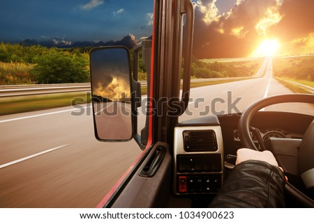 Truck dashboard with driver's hand on the steering wheel and side rear-view mirror on the countryside road against night sky with sunset #1034900623