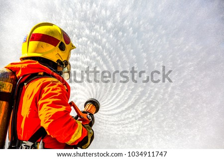 Fireman or Firemen in fire fighting equipment, Firefighter using extinguisher and spray water from hose for fire fighting, Firefighter spraying high pressure water to fire with copy space.