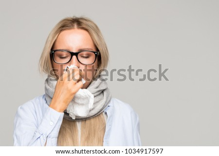 Beautiful upset young blonde woman with glasses, shirt, wrapped scarf with napkin blowing nose, closed eyes, front view/ Sick desperate female has flu/ Rhinitis, cold, sickness, allergy concept/  Royalty-Free Stock Photo #1034917597