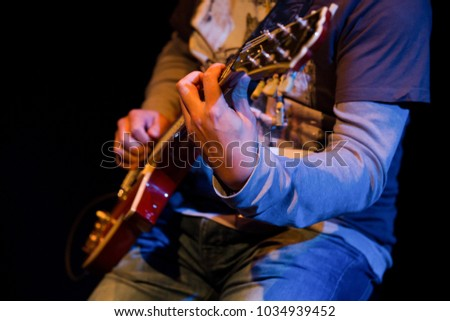 Concept: Talented people doing what they love. Electric guitar player on a dark background. Playing at a music gig. Grunge, Rock and Roll, Alternative Rock Band.