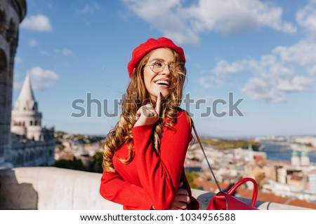 Outdoor portrait of inviting brown-haired girl in beret looking away with smile and touching chin. Photo of laughing french lady in glasses standing on blue sky background.