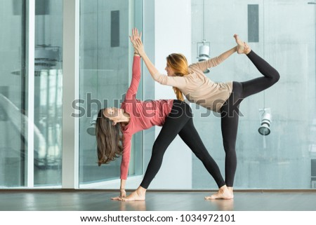 pregnant woman doing yoga exercise with teacher #1034972101