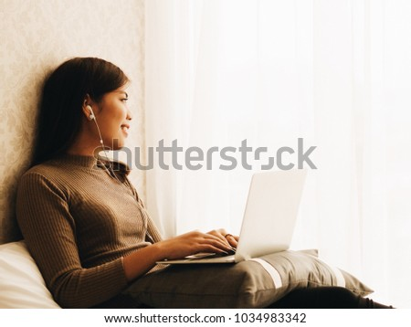 Beautiful Asian woman laying on sofa and using laptop working at her home. #1034983342