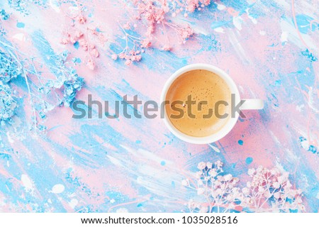 Cup of coffee and flowers on colorful table top view. Flat lay style. Creative breakfast for Woman day. Punchy pastel.