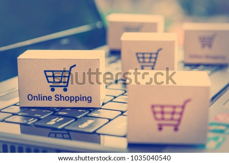 Online shopping / ecommerce and delivery service concept : Paper cartons with a shopping cart or trolley logo on a laptop keyboard, depicts customers order things from retailer sites via the internet. #1035040540