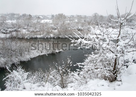 Beautiful winter scene on river after heavy snowfall. Branches of trees and shrubs loaded with snow after heavy snowfall. #1035042325