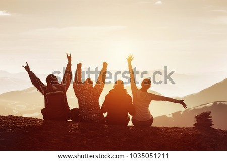 Group of four happy friends is having fun with raised hands against sunset mountains #1035051211
