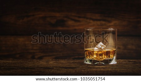 Whisky or whiskey or bourbon with ice on wood background #1035051754