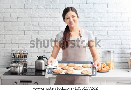Woman holding tray with cookies in kitchen. Fresh from oven #1035159262