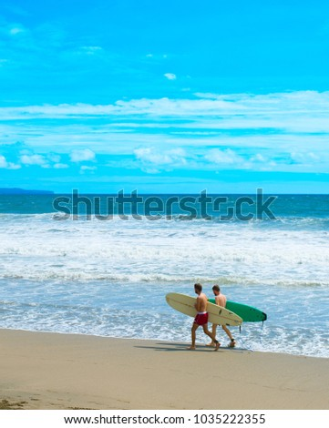 CANGGU, BALI ISLAND, INDONESIA - JAN 19, 2017: Surfers walking with surfboard on the beach. Bali island is one of the worlds best surfing destinations #1035222355