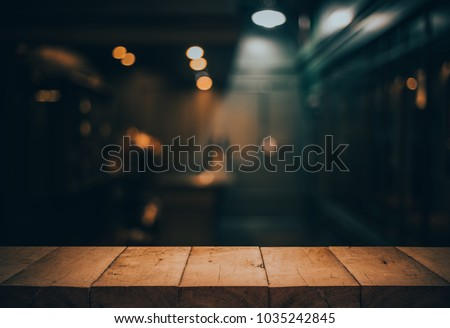 Wood table top on blurred of counter cafe shop with light bulb.Background for montage product display or design key visual layout. #1035242845