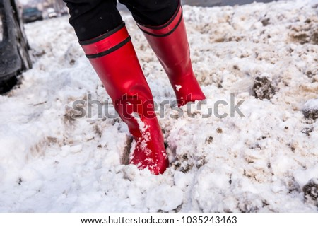 Girl in red boots in deep snow. Winter concept #1035243463