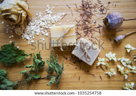 Handmade spa soap bars with natural ingredients. Organic soap making, skin care. Dried  herbs, oats, rose blossoms on wooden vintage background. Spa treatments. Royalty-Free Stock Photo #1035254758